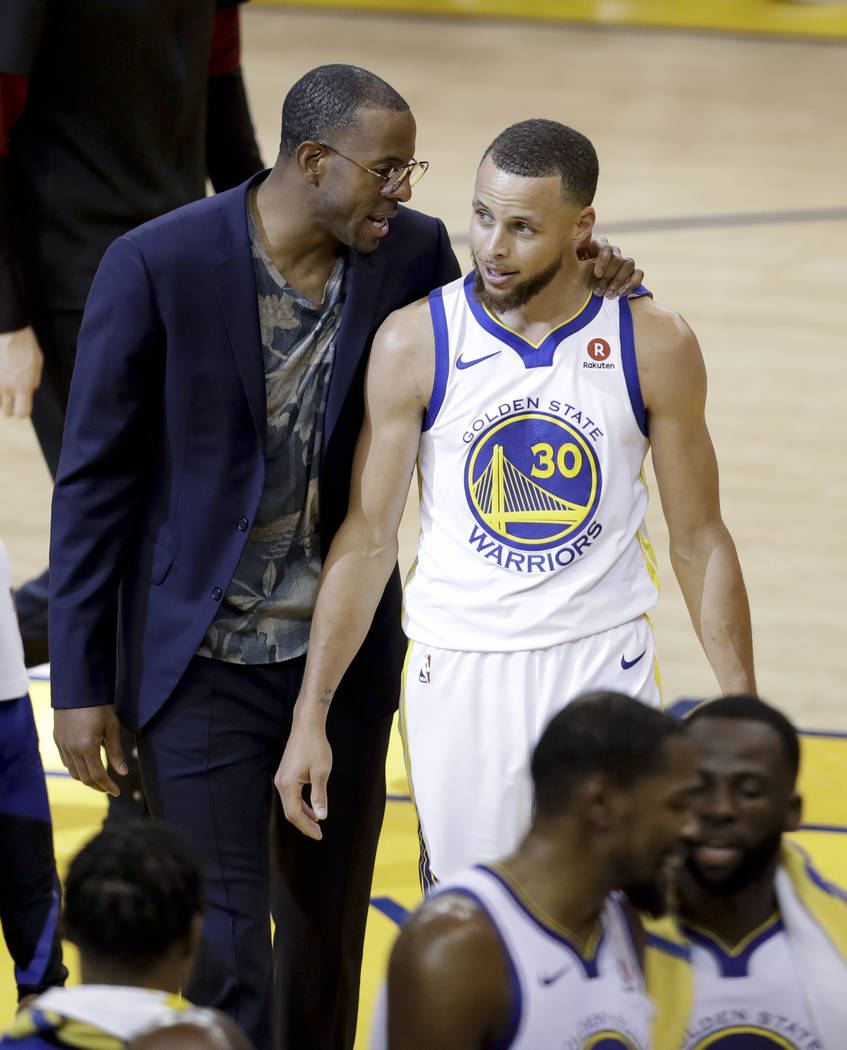 Golden State Warriors guard Stephen Curry (30) walks with injured forward Andre Iguodala, in suit, after scoring against the Cleveland Cavaliers during the first half of Game 1 of basketball's NBA ...