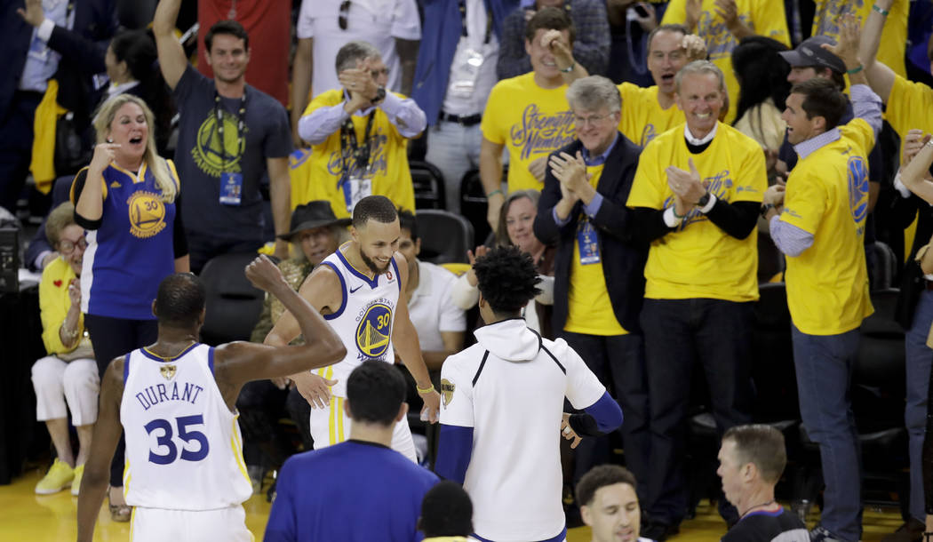 Golden State Warriors guard Stephen Curry (30) is congratulated by teammates after scoring against the Cleveland Cavaliers during the first half of Game 1 of basketball's NBA Finals in Oakland, Ca ...