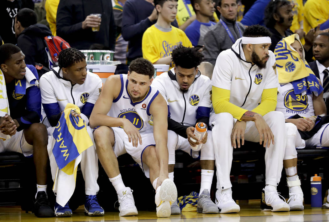 Golden State Warriors guard Klay Thompson (11) sits on the bench with teammates during the first half of Game 1 of basketball's NBA Finals against the Cleveland Cavaliers in Oakland, Calif., Thurs ...