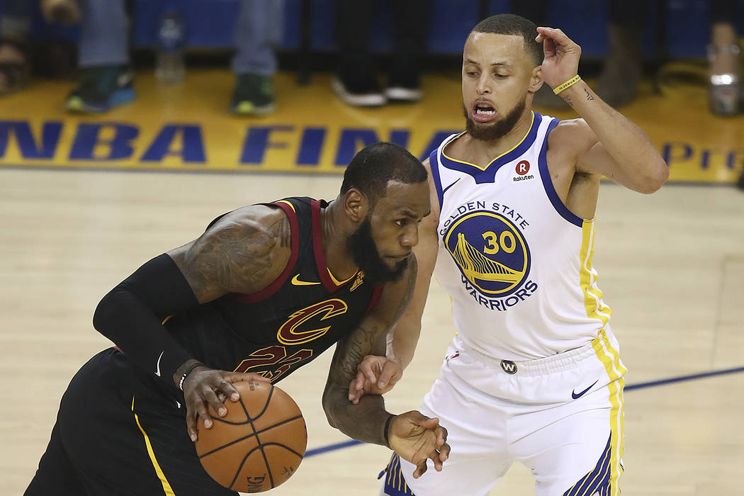 Cleveland Cavaliers forward LeBron James, left, drives against Golden State Warriors guard Stephen Curry during the first half of Game 1 of basketball's NBA Finals in Oakland, Calif., Thursday, Ma ...