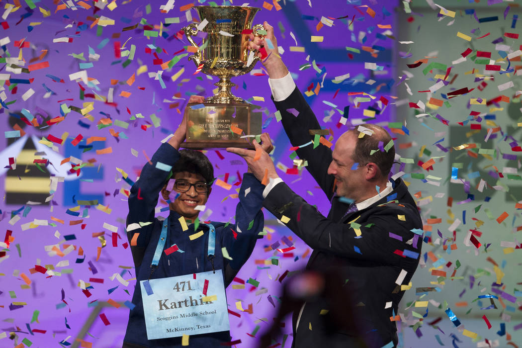 Karthik Nemmani, 14, from McKinney, Texas, is presented with the Scripps National Spelling Bee trophy by Adam Symson, president and CEO, E.W. Scripps Company, after he won the bee, in Oxon Hill, M ...