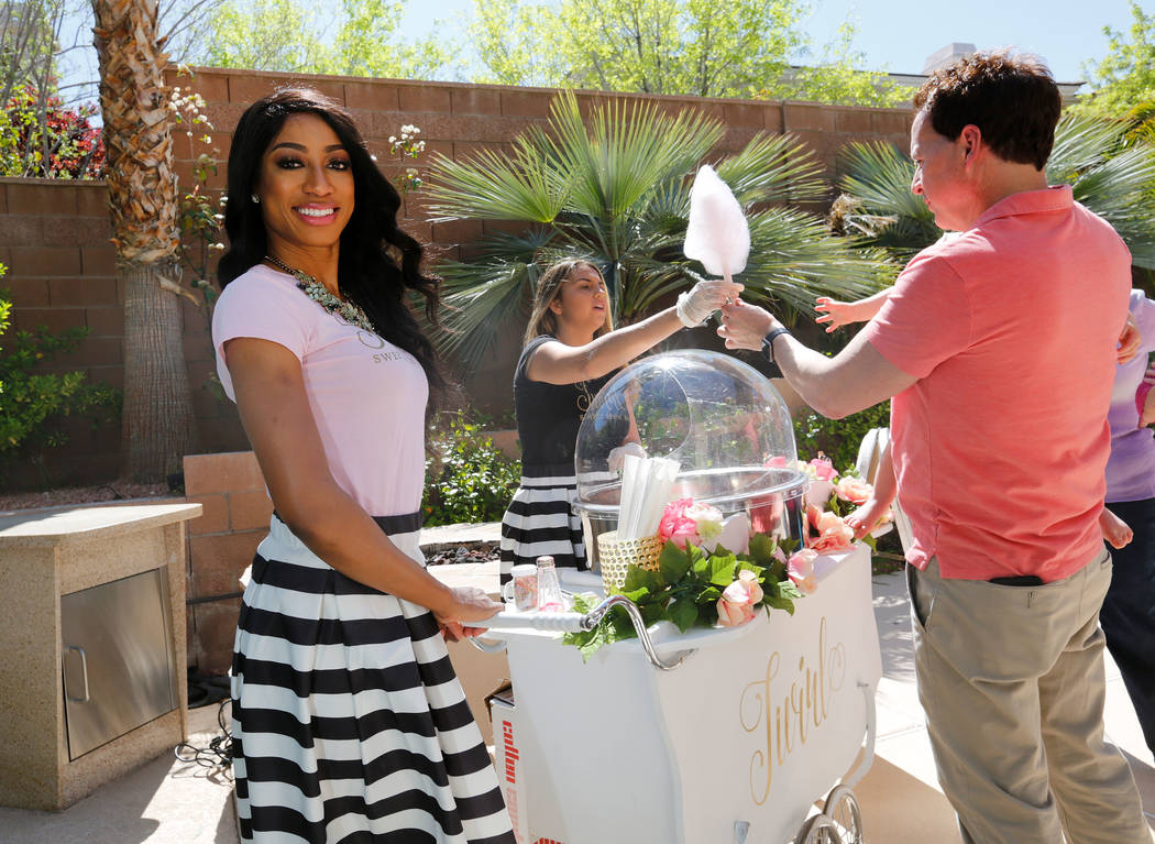 Twirl Cotton Candy owner Natalie Winslow, left, stands by her cart during Gianna Day's first birthday party in Summerlin, Sunday, April 8, 2018, as Twirlette Sidney Morris of Twirl Cotton Candy, b ...