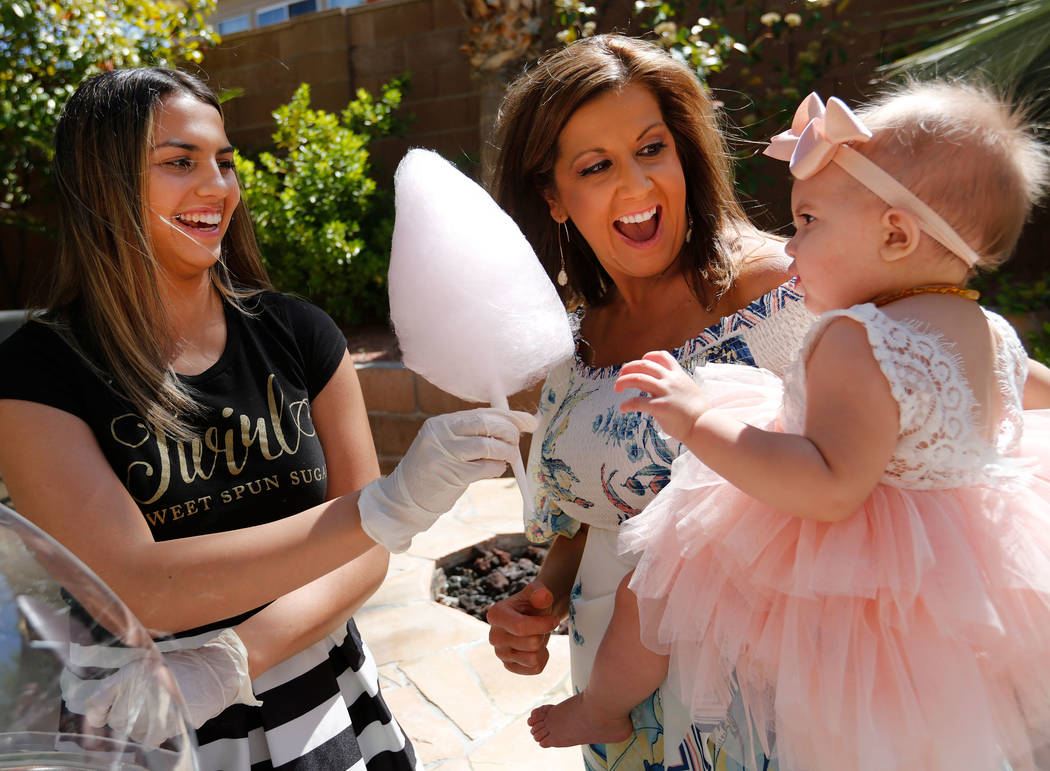 Donita Day, center, and her daughter Gianna, 1, receive a cotton candy from Twirlette Sidney Morris of Twirl Cotton Candy, left, during Gianna's first birthday party in Summerlin, Sunday, April 8, ...