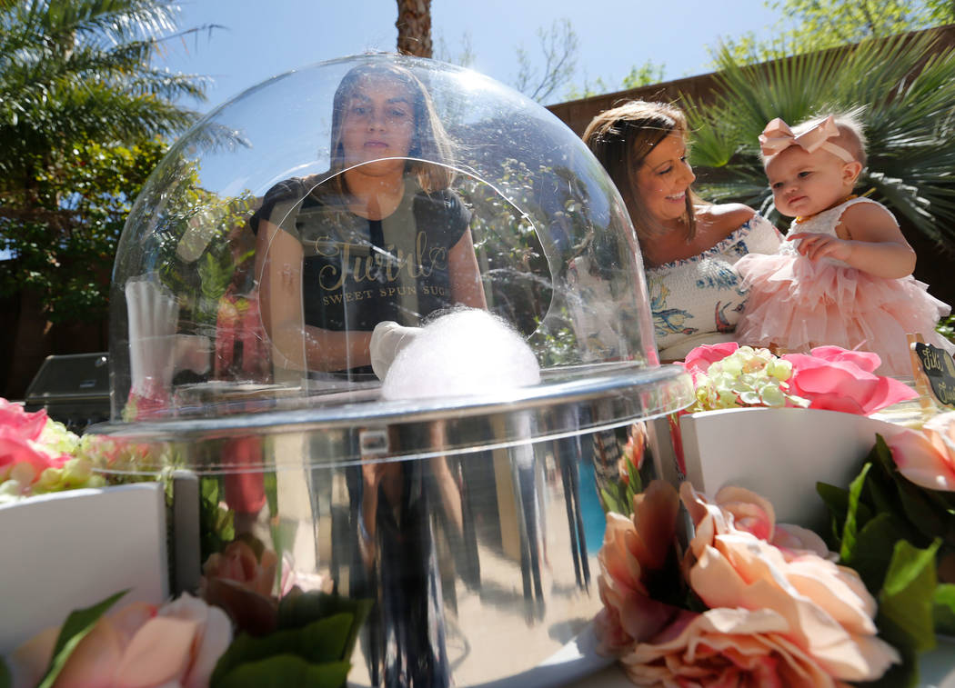 Twirlette Sidney Morris of Twirl Cotton Candy, left, makes a cotton candy as Donita Day, center, holds her daughter Gianna, 1, during Gianna's first birthday party in Summerlin, Sunday, April 8, 2 ...
