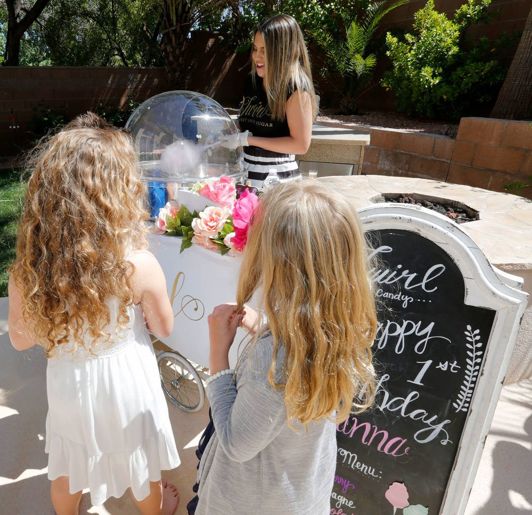 Twirlette Sidney Morris of Twirl Cotton Candy, center, makes a cotton candy during Gianna Day's first birthday party in Summerlin, Sunday, April 8, 2018. Chitose Suzuki Las Vegas Review-Journal @c ...