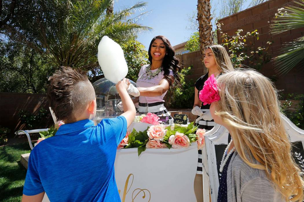 Drew Nicholson, 5 of Las Vegas, left, receives a cotton candy from Twirl Cotton Candy owner Natalie Winslow, center, during Gianna Day's first birthday party in Summerlin, Sunday, April 8, 2018, a ...