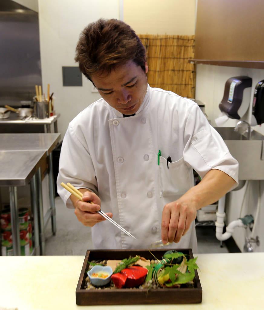 Kaiseki Yuzu's Kaoru Azeuchi works on an expression of the season known as the Hassun course.