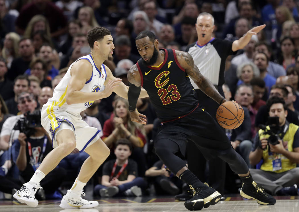 Cleveland Cavaliers' LeBron James is defended by Golden State Warriors' Klay Thompson during the first half of Game 4 of basketball's NBA Finals, Friday, June 8, 2018, in Cleveland. (AP Photo/Tony ...