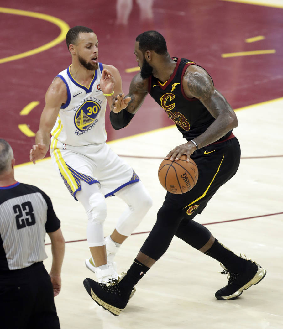 Golden State Warriors' Stephen Curry defends against Cleveland Cavaliers' LeBron James during the first half of Game 4 of basketball's NBA Finals, Friday, June 8, 2018, in Cleveland. (AP Photo/Ton ...