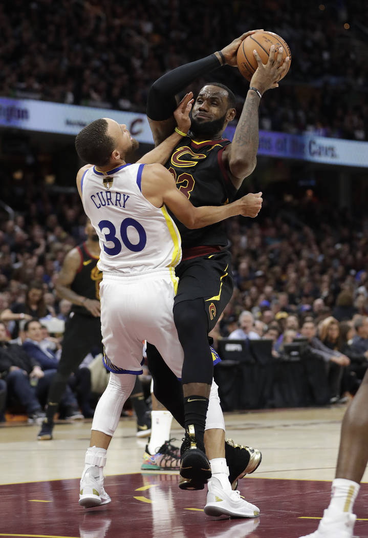 Cleveland Cavaliers' LeBron James is called for a charging foul against Golden State Warriors' Stephen Curry during the second half of Game 4 of basketball's NBA Finals, Friday, June 8, 2018, in C ...