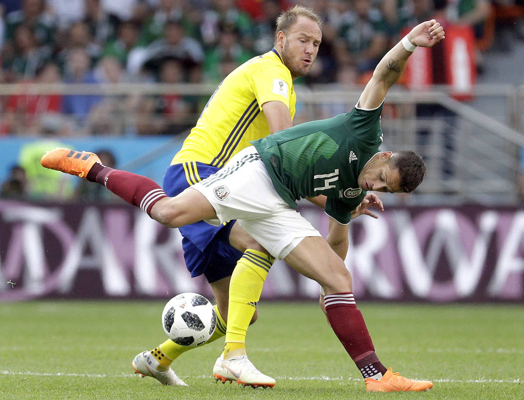 Sweden's Andreas Granqvist, rear, and Mexico's Javier Hernandez, front, challenge for the ball during the group F match between Mexico and Sweden, at the 2018 soccer World Cup in the Yekaterinburg ...