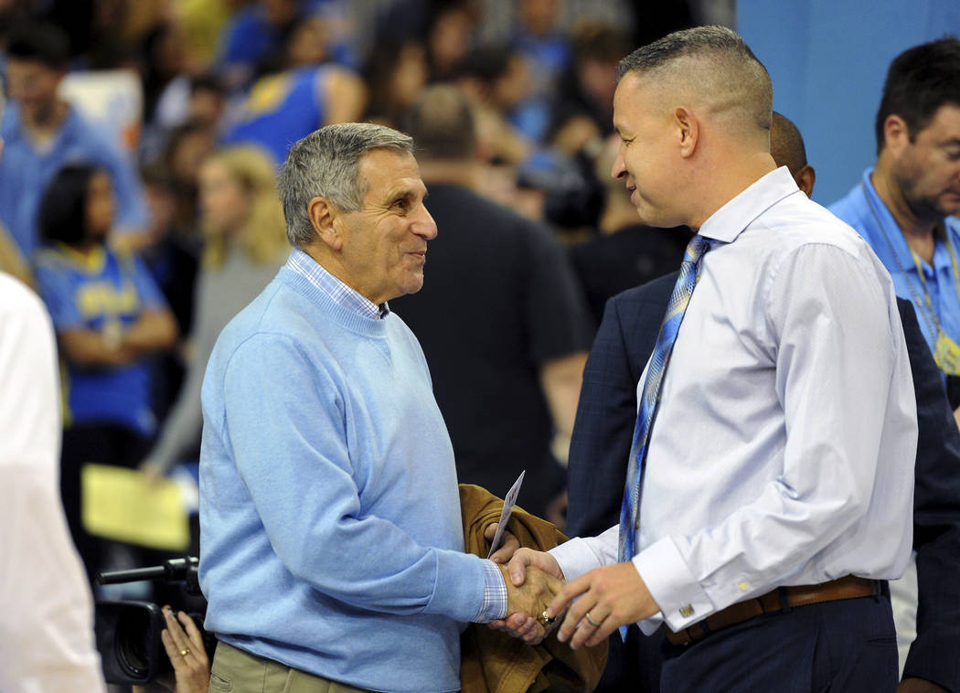 Jim Harrick, left, who coached UCLA's 1994-95 national championship team, greets UCLA assistant coach David Grace before the UCLA-Arizona State NCAA college basketball game in Los Angeles, Thursda ...