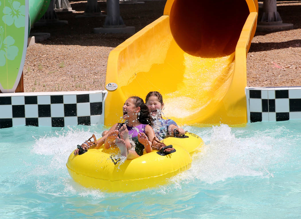Sisters Midnight, 10, left, and London, 13, exit a water slide into a pool at Cowabunga Bay water park in Henderson Wednesday, May 30, 2018. K.M. Cannon Las Vegas Review-Journal @KMCannonPhoto