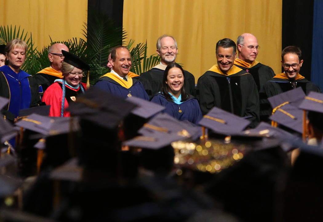Chancellor of Western Governors University of Nevada, Dr. Spencer Stewart, right and Gov. Brian Sandoval, second right, attend WGU's master's degree graduation ceremony at the Thomas & Mack Ce ...
