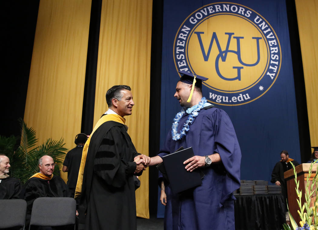 Cameron Fox of Las Vegas, right, shakes hand with Gov. Brian Sandoval after receiving his diploma during the master's degree graduation ceremony of Western Governors University of Nevada&#xa ...