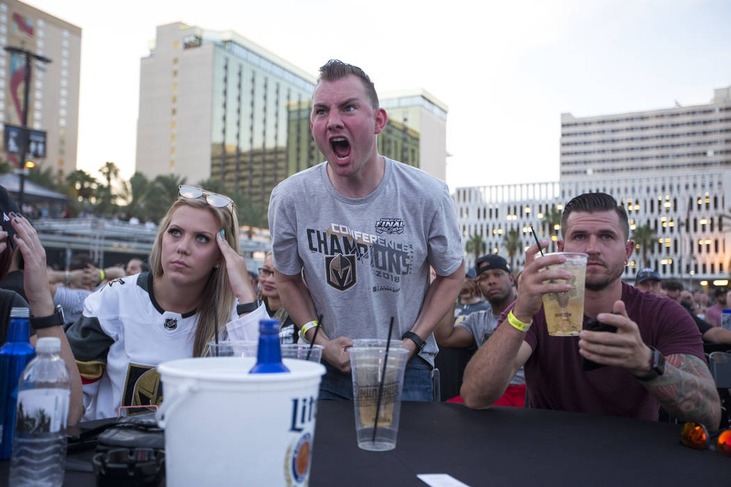 Vegas Golden Knights fans, from left, Shaylene Scarlett, David Dennison and Billy McAlpine react to a play during a watch party for Game 3 of the Stanley Cup Final between the Golden Knights and t ...