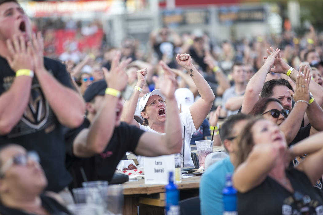 Golden Knights fans Lara Borel, center, reacts to a play during a watch party for Game 3 of the Stanley Cup Final between the Golden Knights and the Washington Capitals at the Downtown Las Vegas E ...