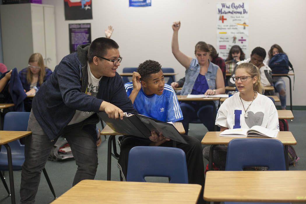 Carlos Hernandez-Munoz points out the answer to D'Andre Burnett and Marykate Springer as a student group leads a presentation in math class at Shadow Ridge High School in Las Vegas, Wednesday, May ...
