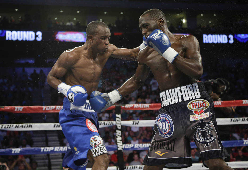 Terence Crawford, right, follows through on a punch to Julius Indongo during the third round of a junior welterweight title unification boxing bout in Lincoln, Neb., Saturday, Aug. 19, 2017. Crawf ...