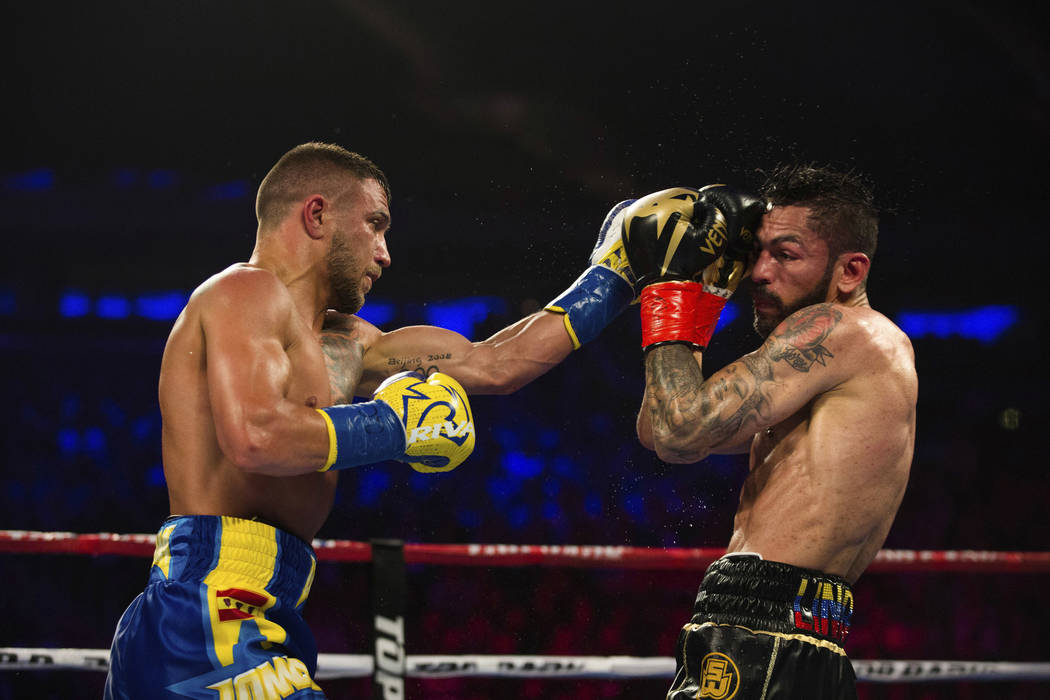 Vasiliy Lomachenko, left, of Ukraine, fights Jorge Linares, of Venezuela, during their WBA lightweight championship boxing match Saturday, May 12, 2018, in New York. (AP Photo/Kevin Hagen)