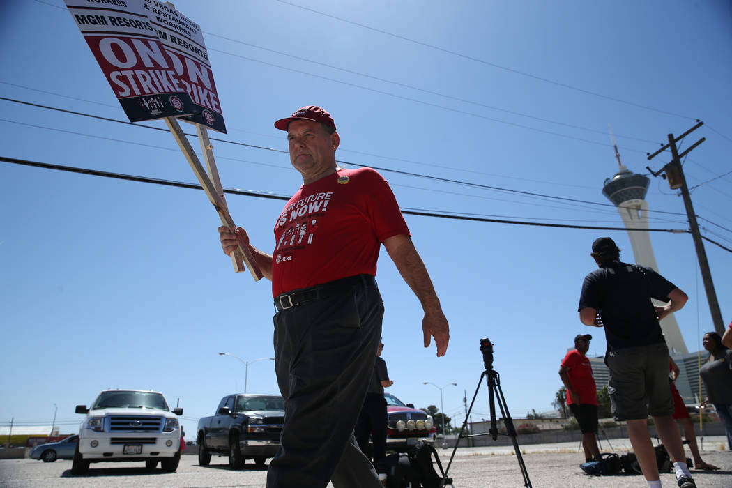 """Culinary Union organizer Guy Locatelli carries strike picket signs at the newly opened """"Strike HQ"""" at the intersection of Wyoming Avenue and Fairfield Avenue in Las Vegas, Friday, Ju ..."""