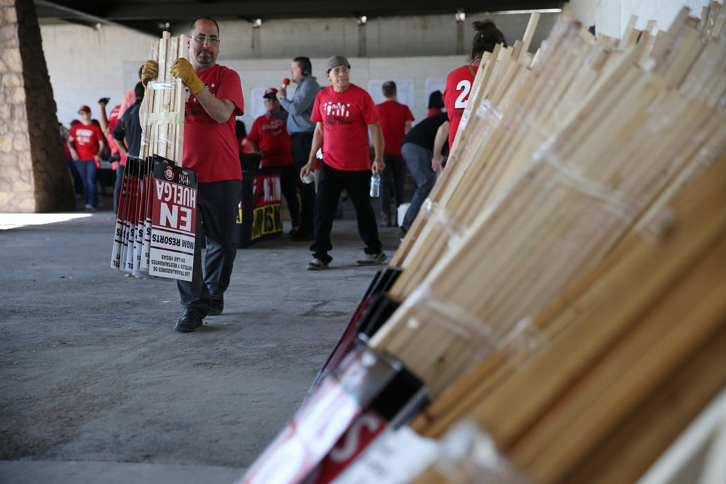 "Culinary Union organizer David Saba carries strike picket signs at the newly opened ""Strike HQ"" at the intersection of Wyoming Avenue and Fairfield Avenue in Las Vegas, Friday, June ..."