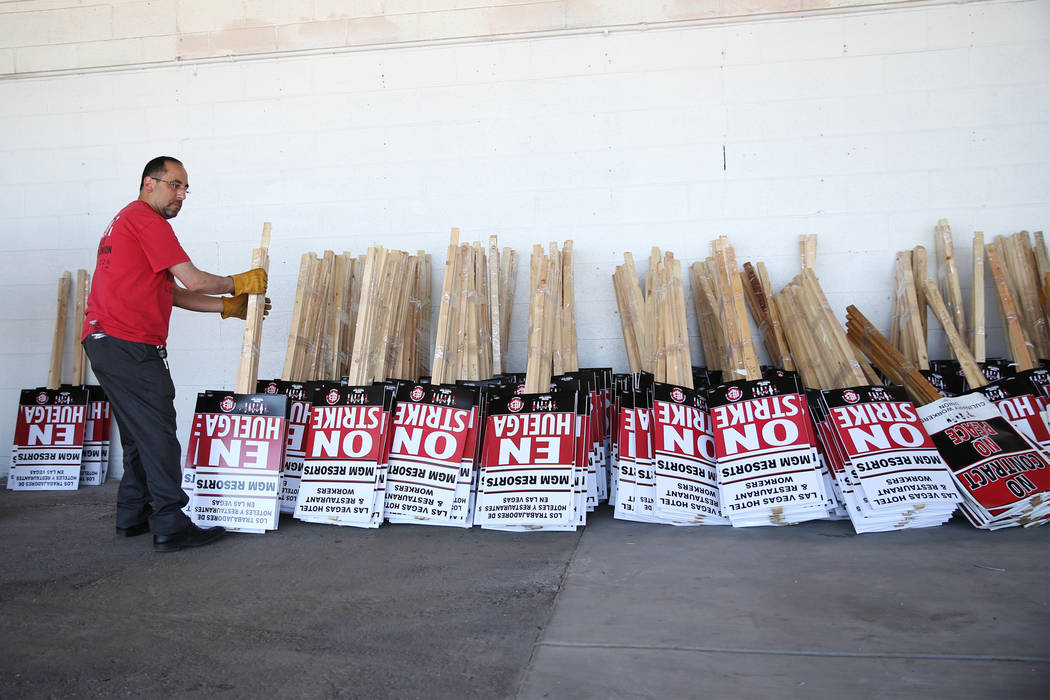 "Culinary Union organizer David Saba moves strike picket signs at the newly opened ""Strike HQ"" at the intersection of Wyoming Avenue and Fairfield Avenue in Las Vegas, Friday, June 1, ..."