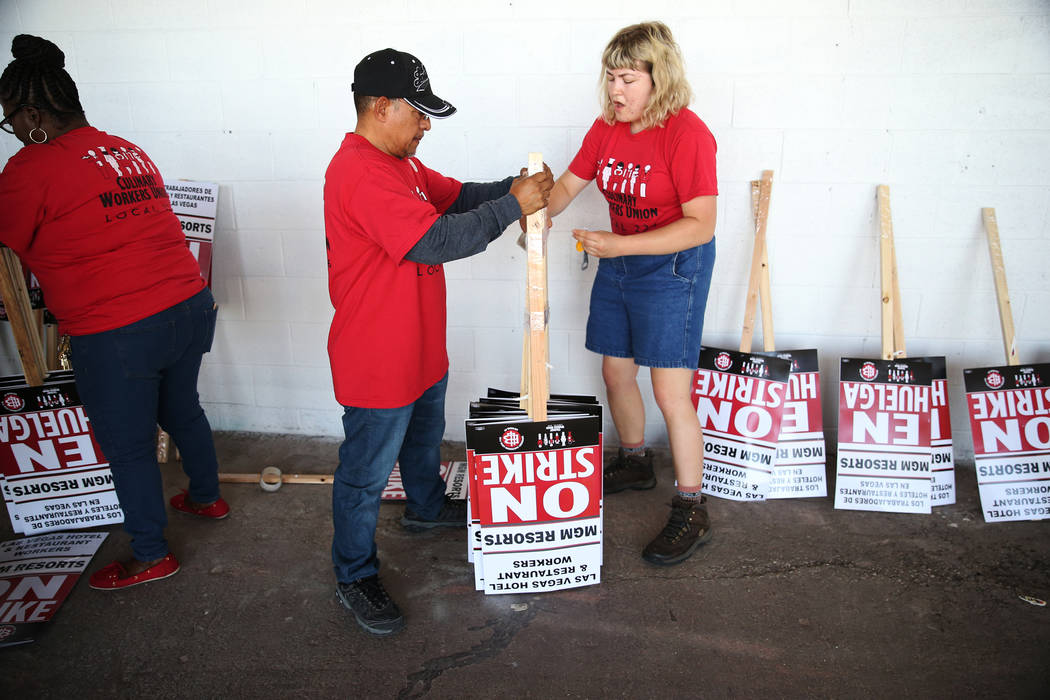 "Culinary Union organizers Jorge Ortiz, left, and Hannah Schmitt wrap together strike picket signs at the newly opened ""Strike HQ"" at the intersection of Wyoming Avenue and Fairfield ..."