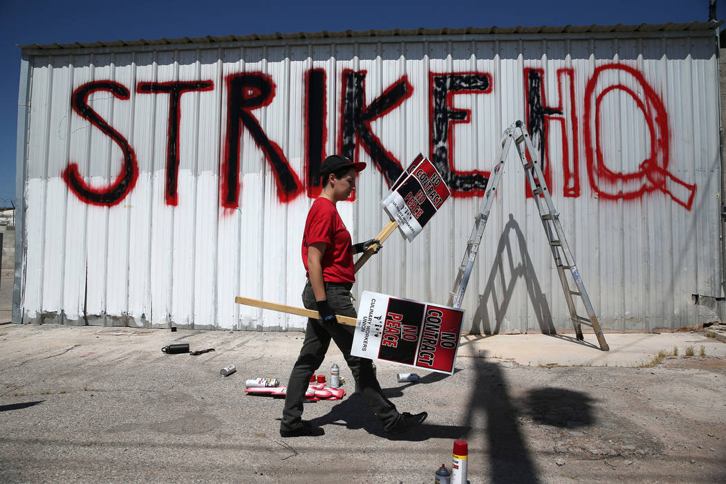 """Culinary Union organizer Lianna Schechter carries strike picket signs at the newly opened """"Strike HQ"""" at the intersection of Wyoming Avenue and Fairfield Avenue in Las Vegas, Friday, ..."""