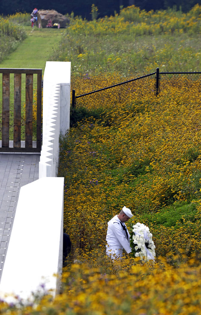 Navy Quartermaster Matthew Konchan of Johnstown, Pa., stands in a field of flowers before a wreath-laying ceremony during a memorial service at the Flight 93 National Memorial on Wednesday in Shan ...