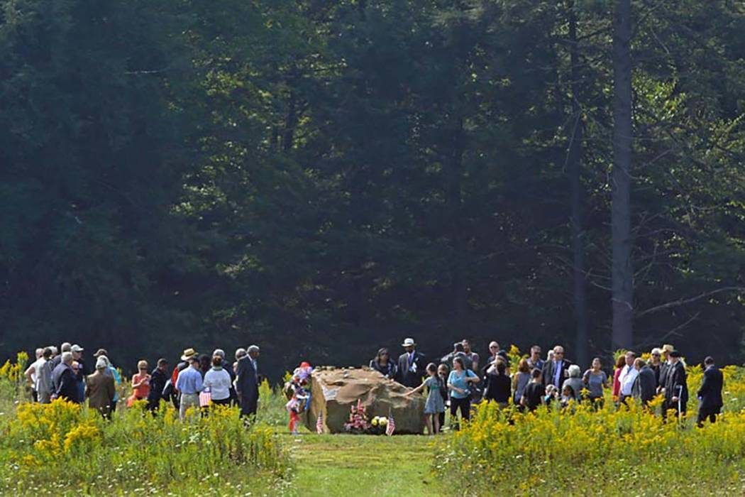 The family and friends of the passengers and crew of Flight 93 gather around a boulder that marks the plane's impact area during a memorial service at the Flight 93 National Memorial, Sept. 11, 20 ...
