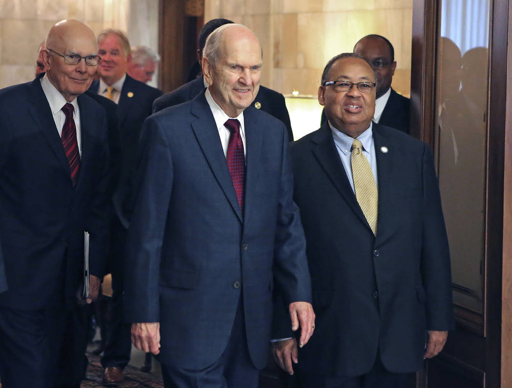 Mormon church President Russell M. Nelson, center, and Leon W. Russell, chairman of the NAACP board of directors, right, walk into a news conference, in Salt Lake City, May 17, 2018. The Mormon ch ...