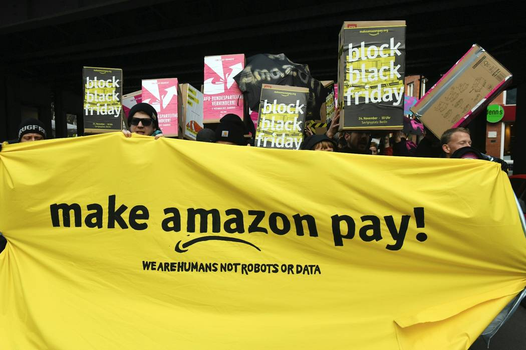 Demonstrators hold a banner and posters during a rally against the online retailer Amazon in Berlin, Germany, Friday, Nov. 24, 2017. A labor union says workers at a half dozen Amazon distribution ...