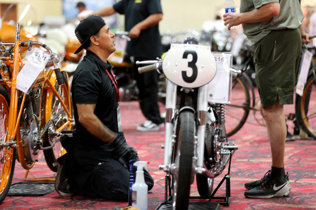Detailer Louis Rodriguez, left, visits with Roland Jacques of Las Vegas as Rodriguez works on a 1956 Mondial F2 during the Mecum Las Vegas Motorcycle Auction at the South Point Friday, June 1, 201 ...