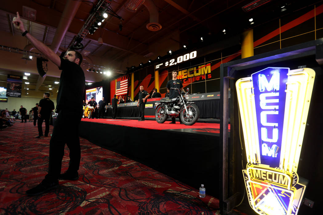 Alex Mcglothlen, left, acknowledges a bid as Aaron Hartley shows a 1971 Harley-Davidson ML-125S Rapido during the Mecum Las Vegas Motorcycle Auction at the South Point Friday, June 1, 2018. K.M. C ...