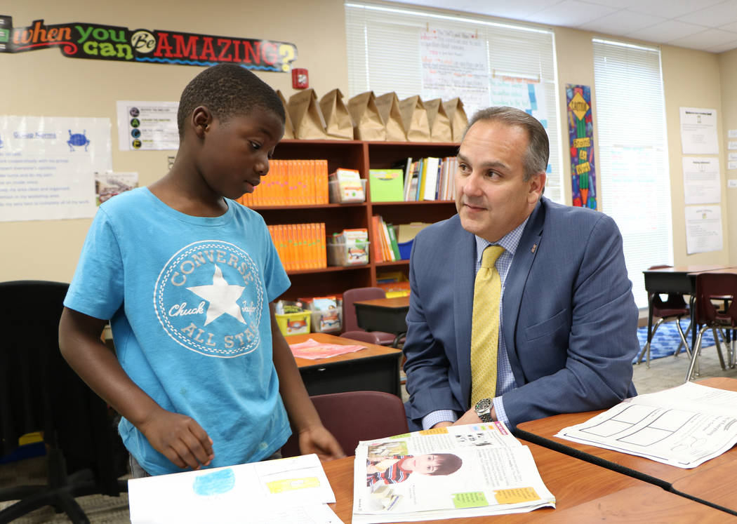 Washington Shores Elementary School student Gregory Hill discusses his essay on ice cream with incoming Clark County Superintendent Jesus Jara during a tour of the Orlando school on Wednesday, Ma ...
