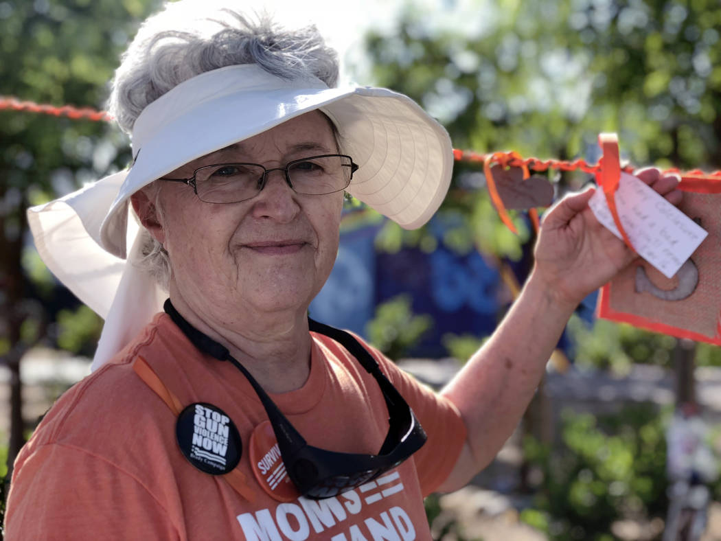 Sara Diss, a member of Moms Demand Action, ties a note in remembrance of a family member affected by gun violence, at the Wear Orange event at the Las Vegas Community Healing Garden on Saturday, J ...