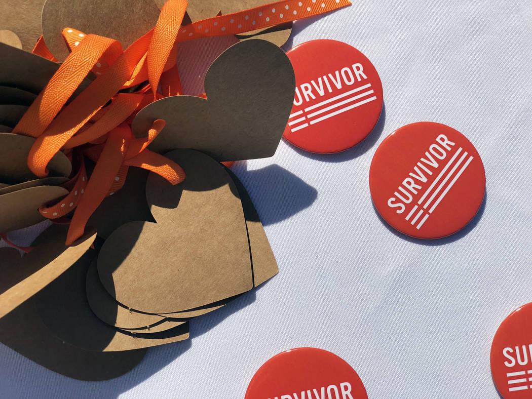 Gun violence prevention group Moms Demand Action hands out survivor pins at the Wear Orange gun violence campaign event at the Las Vegas Community Healing Garden on Saturday, June 2, 2018. (Rio La ...