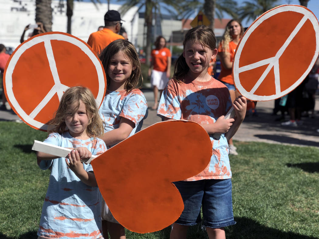 The Oseas family holds up their signs at the Wear Orange gun violence prevention event at the Las Vegas Community Healing Garden on Saturday, June 2, 2018. (Rio Lacanlale/Las Vegas Review-Journal)