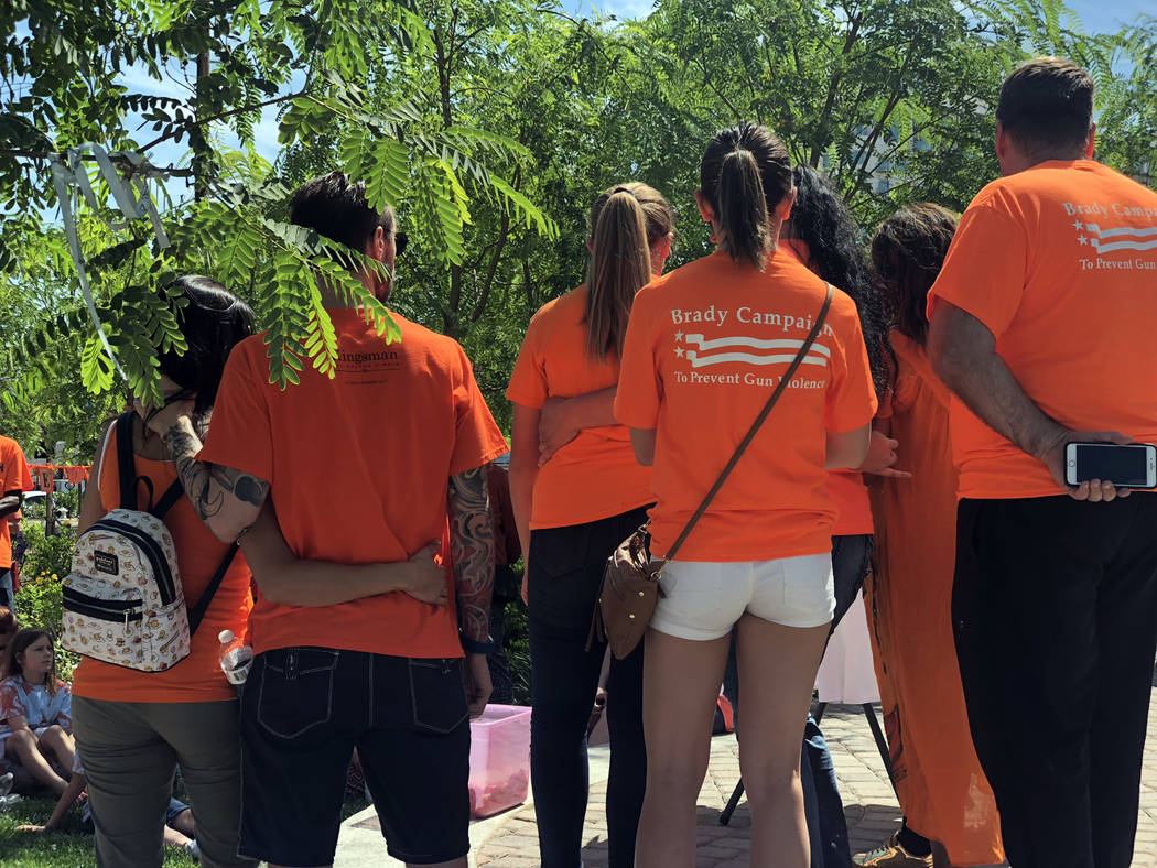 Las Vegas shooting survivors join fellow survivor Christine Caria on stage as she delivers her speech at the Wear Orange gun violence prevention campaign at the Las Vegas healing garden on Saturda ...