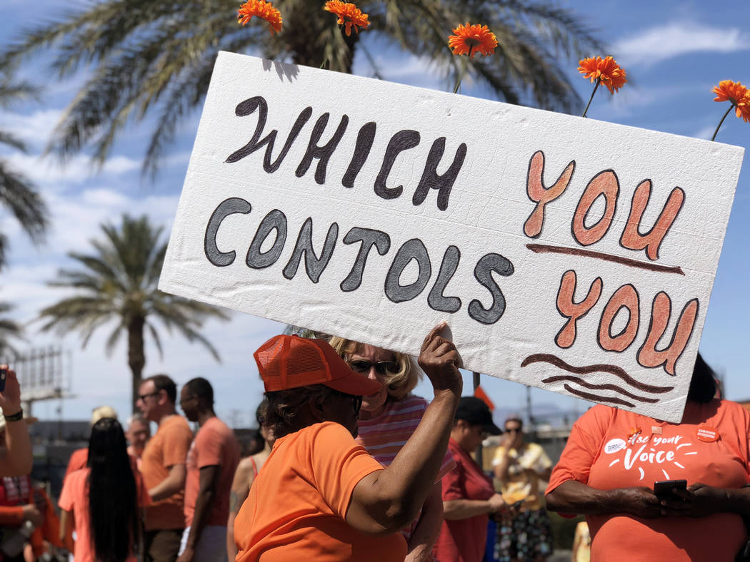 Althea Parker, a Las Vegas resident, holds up her sign at the Wear Orange gun violence prevention campaign event at the Las Vegas Community Healing Garden on Saturday, June 2, 2018. (Rio Lacanlale ...