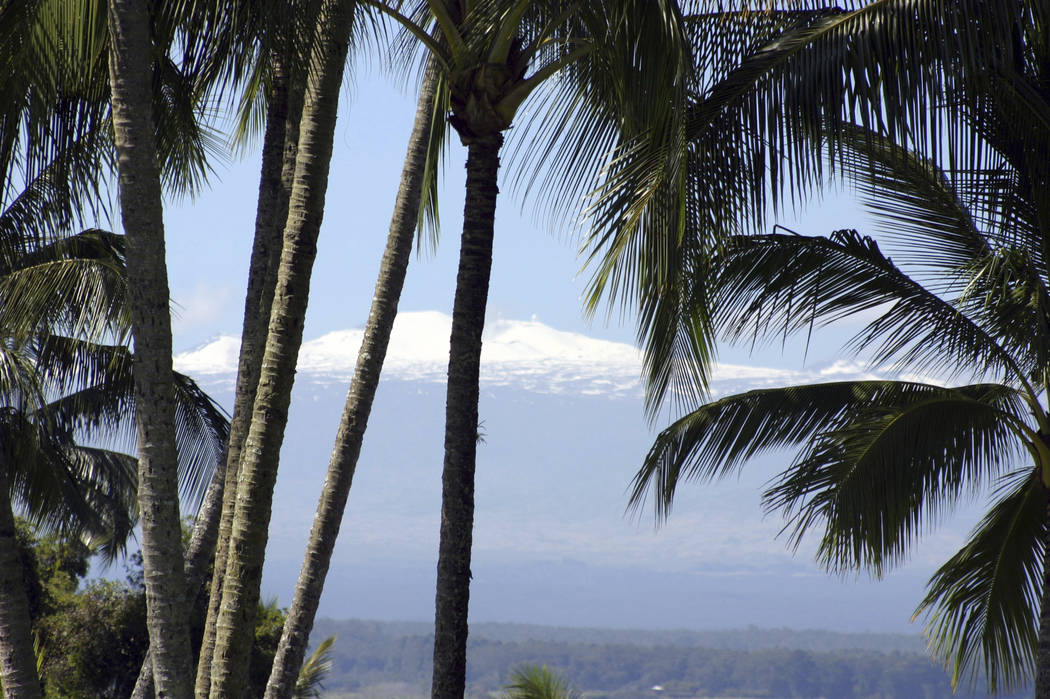 A snow-capped Mauna Kea volcano rises in the background from Hilo, Hawaii, in 2005. (AP/Photo Tim Wright, File)