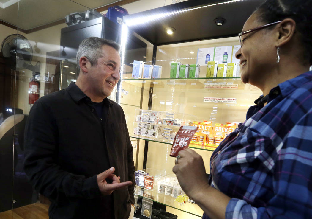Adam Smith, left, founder and executive director, Oregon Craft Cannabis Alliance, is shown a variety of edible marijuana products by Tree PDX marijuana shop owner Brooke Smith at her shop in Portl ...