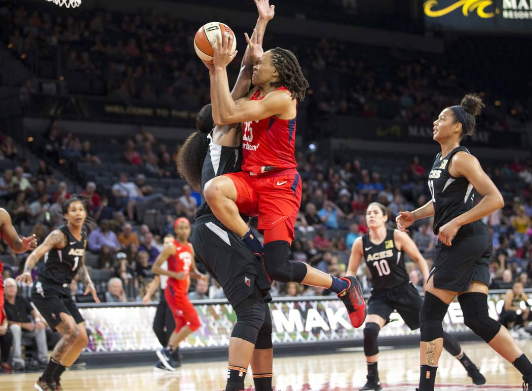 Washington Mystics forward Monique Currie (25) gets fouled by Las Vegas Aces center Kelsey Bone (3) in the first half of a WNBA basketball game at the Mandalay Bay Events Center in Las Vegas on Fr ...