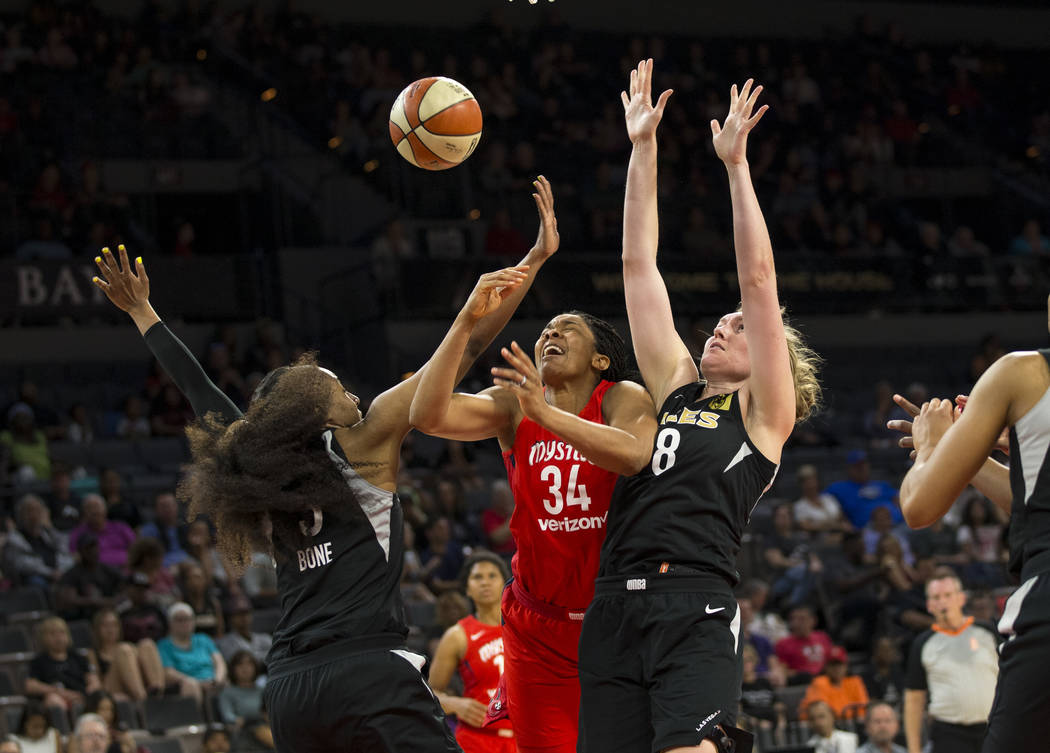 Washington Mystics center Krystal Thomas (34) gets blocked by Las Vegas Aces centers Kelsey Bone (3) and Carolyn Swords (8) in the first half of a WNBA basketball game at the Mandalay Bay Events C ...