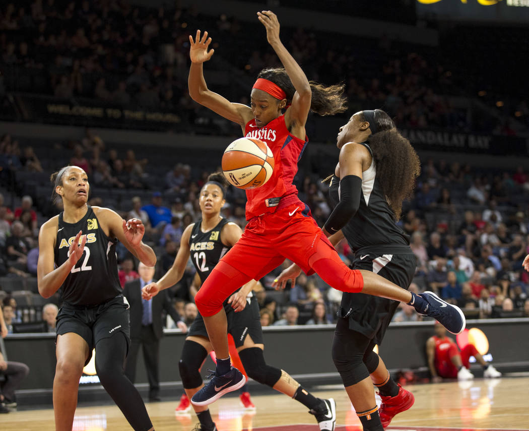 Washington Mystics guard Shatori Walker-Kimbrough (32) gets the ball stripped by Las Vegas Aces center Kelsey Bone (3) in the first half of a WNBA basketball game at the Mandalay Bay Events Center ...