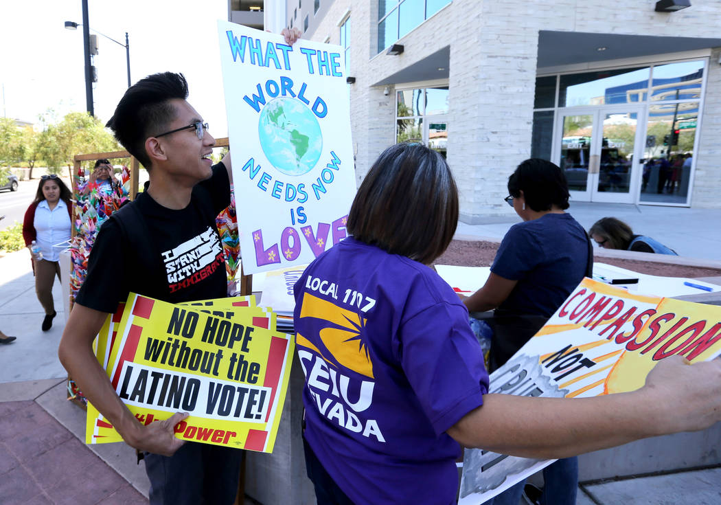 Karl Catarata, left, and Grace Vergara-Mactal hand out signs during a National Day of Action protest outside the Federal Justice Tower where U.S. Immigration and Customs Enforcement has offices Fr ...