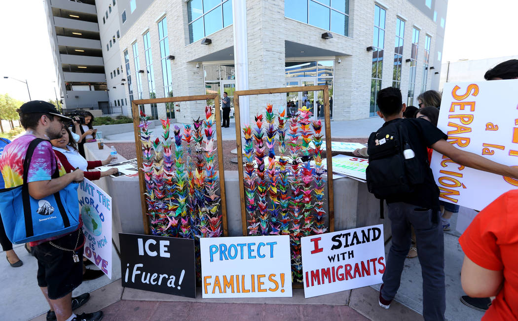 Organizers hand out signs during a National Day of Action protest outside the Federal Justice Tower where U.S. Immigration and Customs Enforcement has offices Friday, June 1, 2018. Several organiz ...
