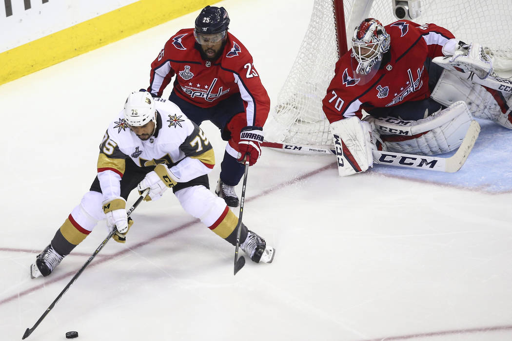 Golden Knights right wing Ryan Reaves (75) controls the puck in front of Washington Capitals right wing Devante Smith-Pelly (25) and goaltender Braden Holtby (70) during the second period of Game ...