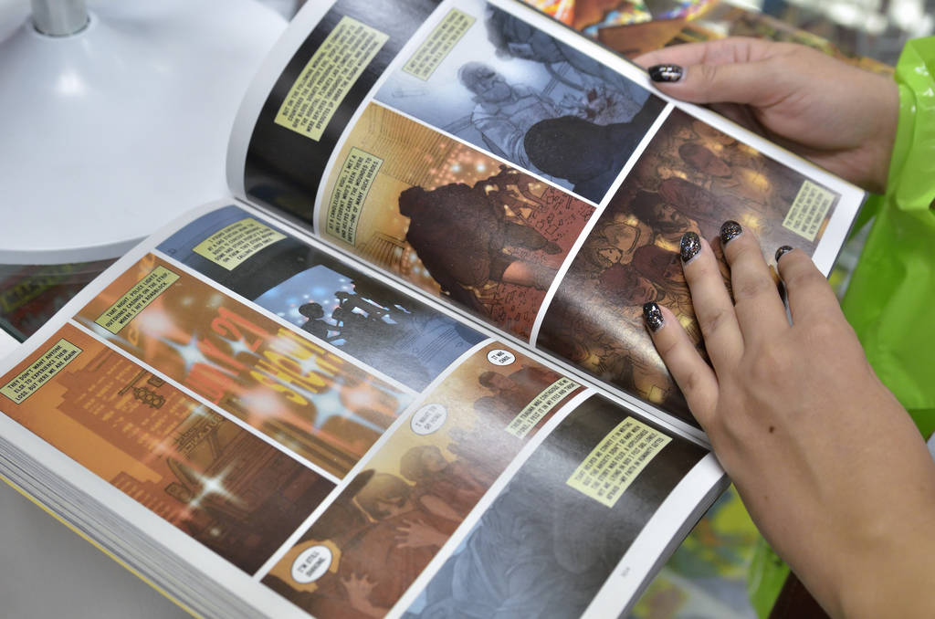 Laura Barrera looks through ÒWhere We Live,Ó a comic book anthology dealing with the Route 91 Harvest Festival shooting, during a book launch and signing at Alternate Reality Comics at 4 ...